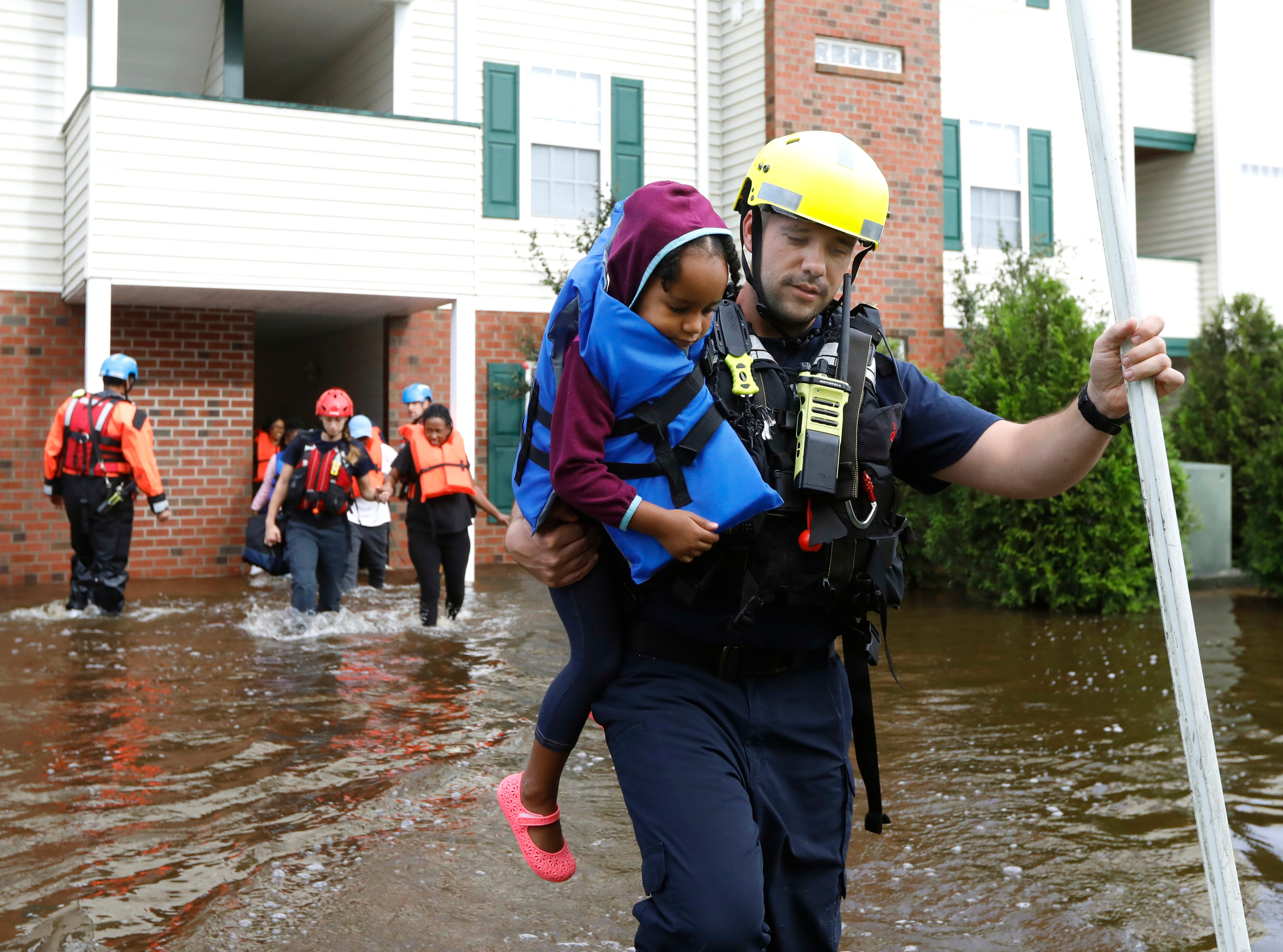 Capt. Steven Barker with Spring Lake Fire Department helps evacuate residents from the Heritage at Fort Bragg Apartments in Spring Lake, N.C., Monday Sept. 17, 2018.