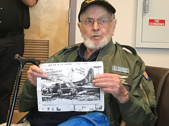 World War II veteran Jules Bernard, of Knoxville, shows a picture from Life magazine of himself at work dismantling a crashed B-17 bomber in August 1942. An arrow points to Bernard on the tail section.