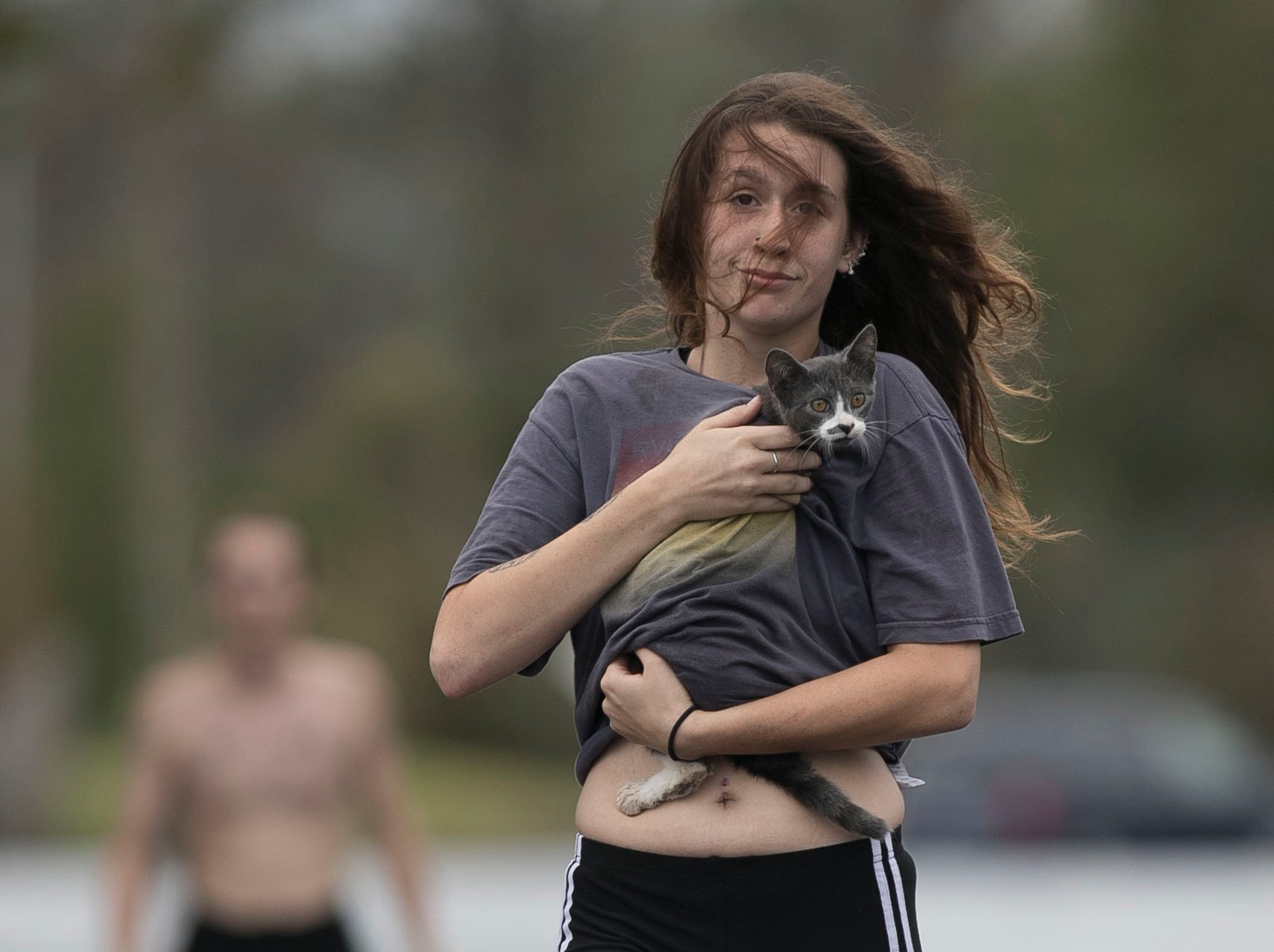 Amanda Mason carries a cat she rescued from her neighborhood off of Nine Foot Road, Sunday, Sept. 16, 2018, in Newport, N.C. Mason and her partner Zack McWilliams visited their damaged home and found the displaced cat and carried it out to safety. Their home was flooded by fast rising water from a tributary of the Newport River on Friday night.