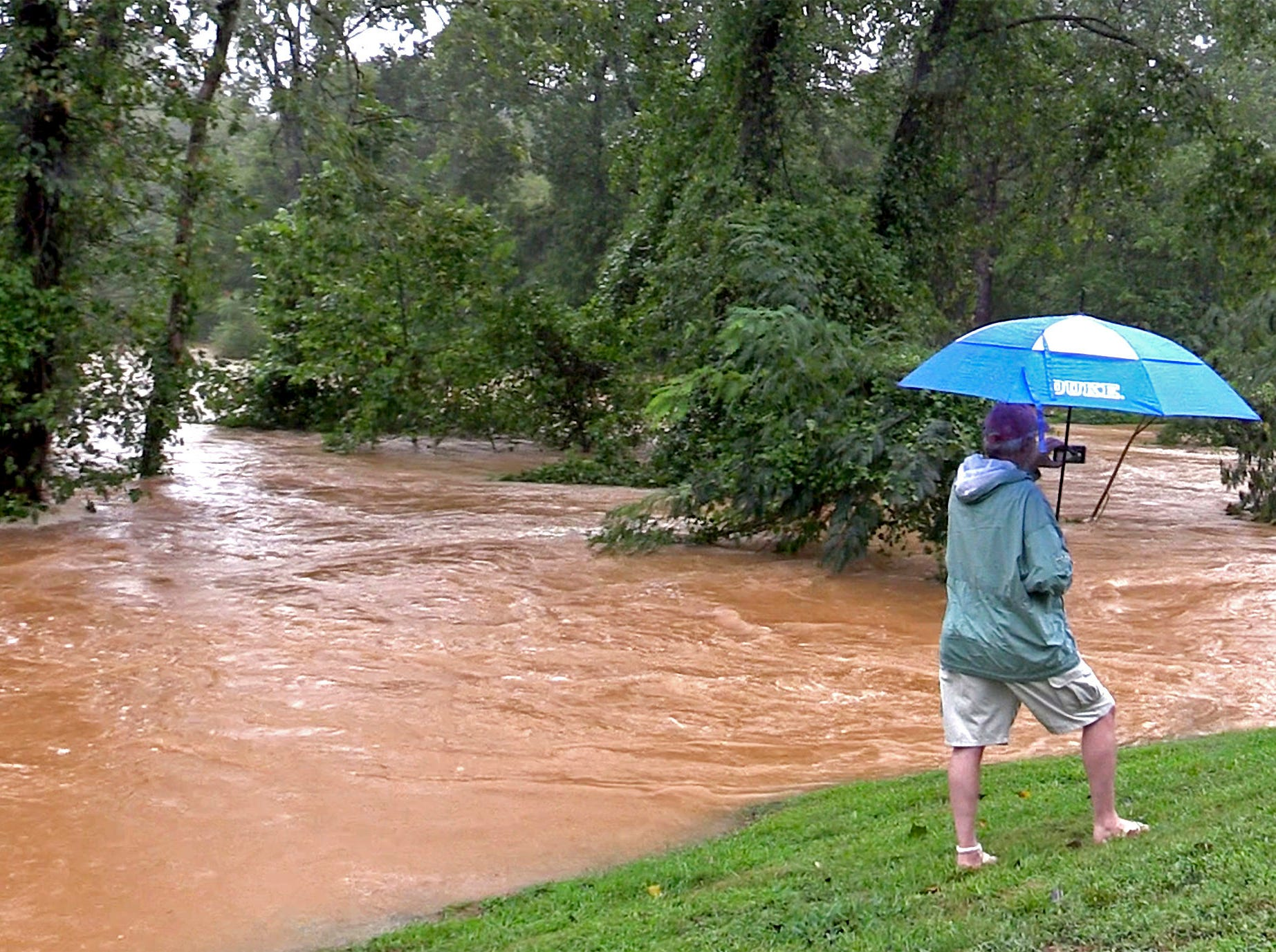 A man photographs the floodwaters of McAlpine Creek along Randolph Road in Charlotte, N.C., on Sunday, Sept. 16, 2018, following Tropical Storm Florence. Florence forced McAlpine Creek from its bed, flooding the popular greenway for walkers and bicyclists.