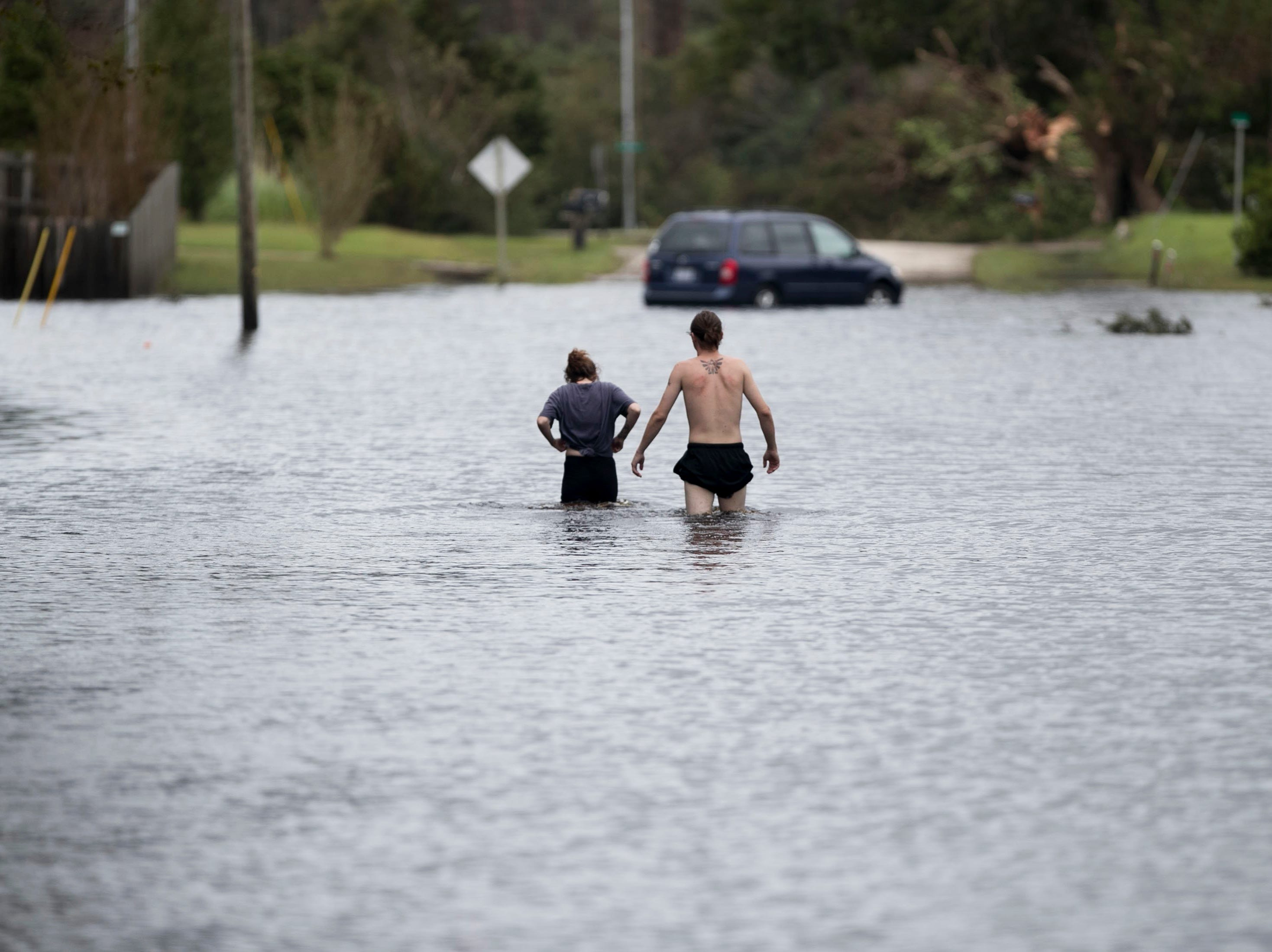 Amanda Mason and Zack McWilliams walk through waist-deep water to take a look at their flooded home off of Nine Foot Road on Sunday, Sept. 16, 2018, in Newport, N.C. They were displaced on Friday night after fast-rising water entered their home from a tributary of the Newport River.