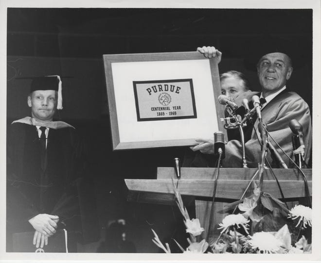 Purdue President Fred Hovde, right, holds a framed Purdue Centennial flag Neil Armstrong, left, took with him on the Apollo 11 mission to the moon. Armstrong gave the flag to Purdue on Jan. 9, 1970, the day the university gave the first man on the moon an honorary doctorate in engineering.