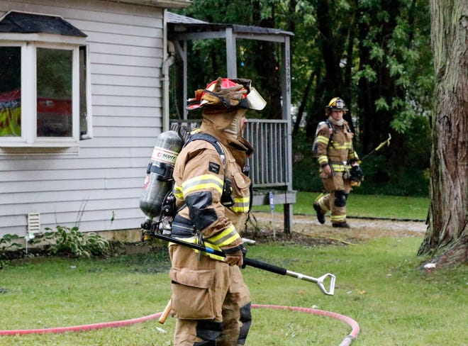 Firefighters walk away from a home Monday afternoon, Sept. 17, 2018, at Fairfield Beach in Walnut Township. The home's resident Tony Vohsine said the house was full of smoke when he get home from work. Millersport Fire Chief Bob Price said a cause of the wasn't immediately known, but that it looked to have started in a utility room or the kitchen. No one was injured in the fire.