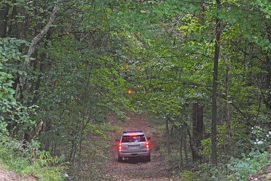 Law enforcement use SUVs to search for Shawn R. Christy on a property in Bellville on Monday morning.