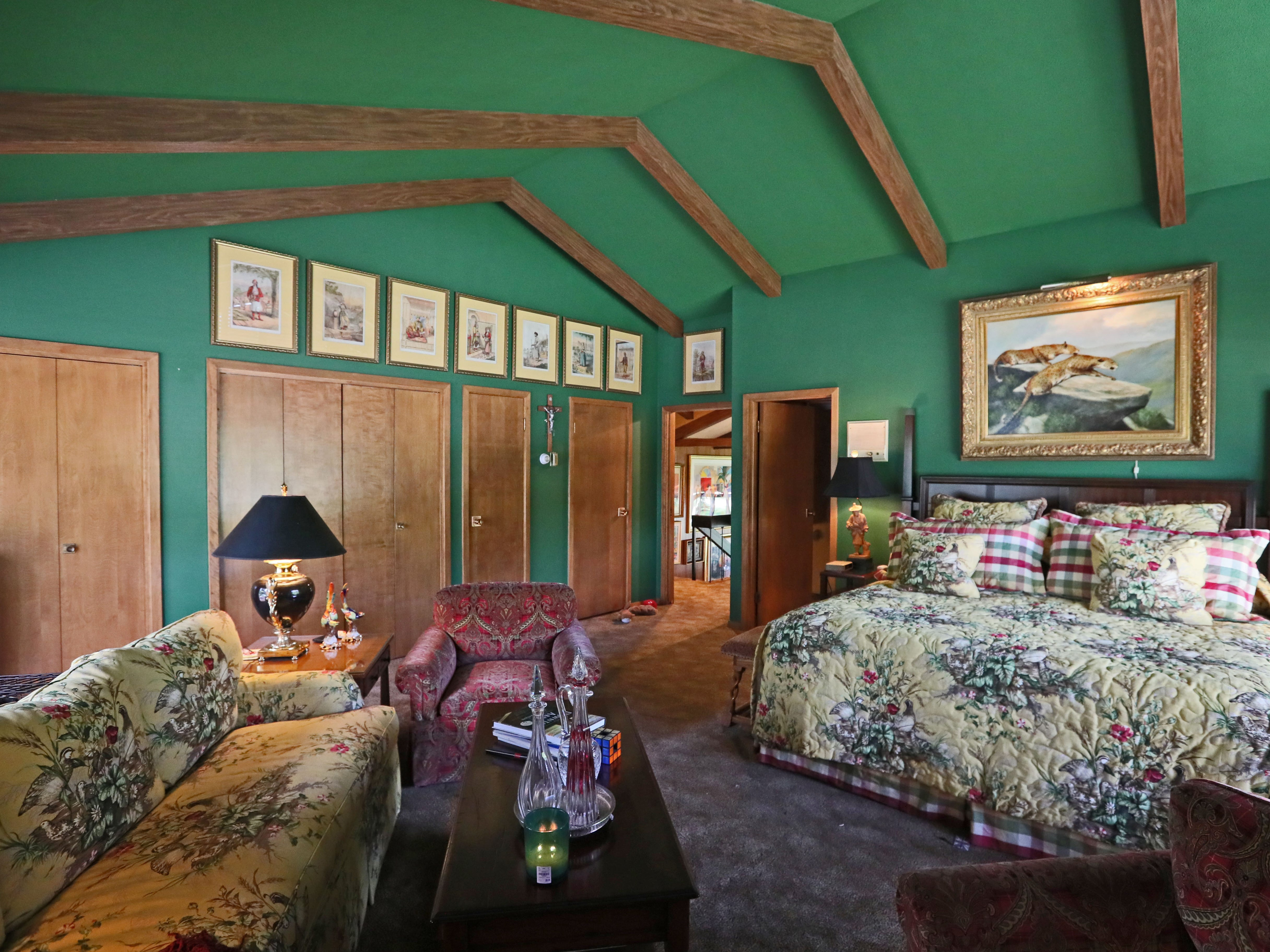 The master bedroom is done in bright green. Vaulted ceilings appear throughout the house.
