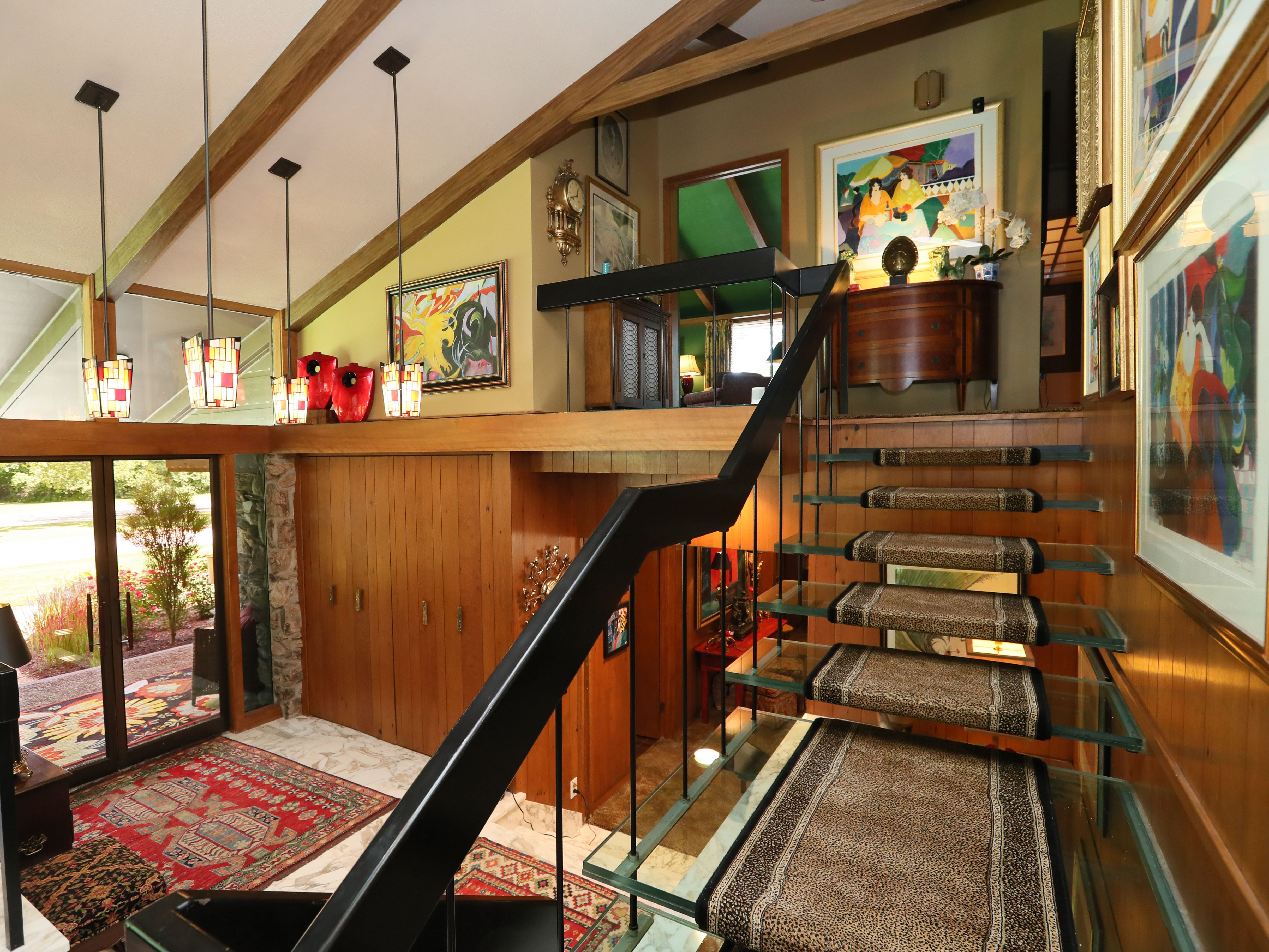 Glass stairs lined with carpet lead to the upper level. Modern art accents the stairway and landing.