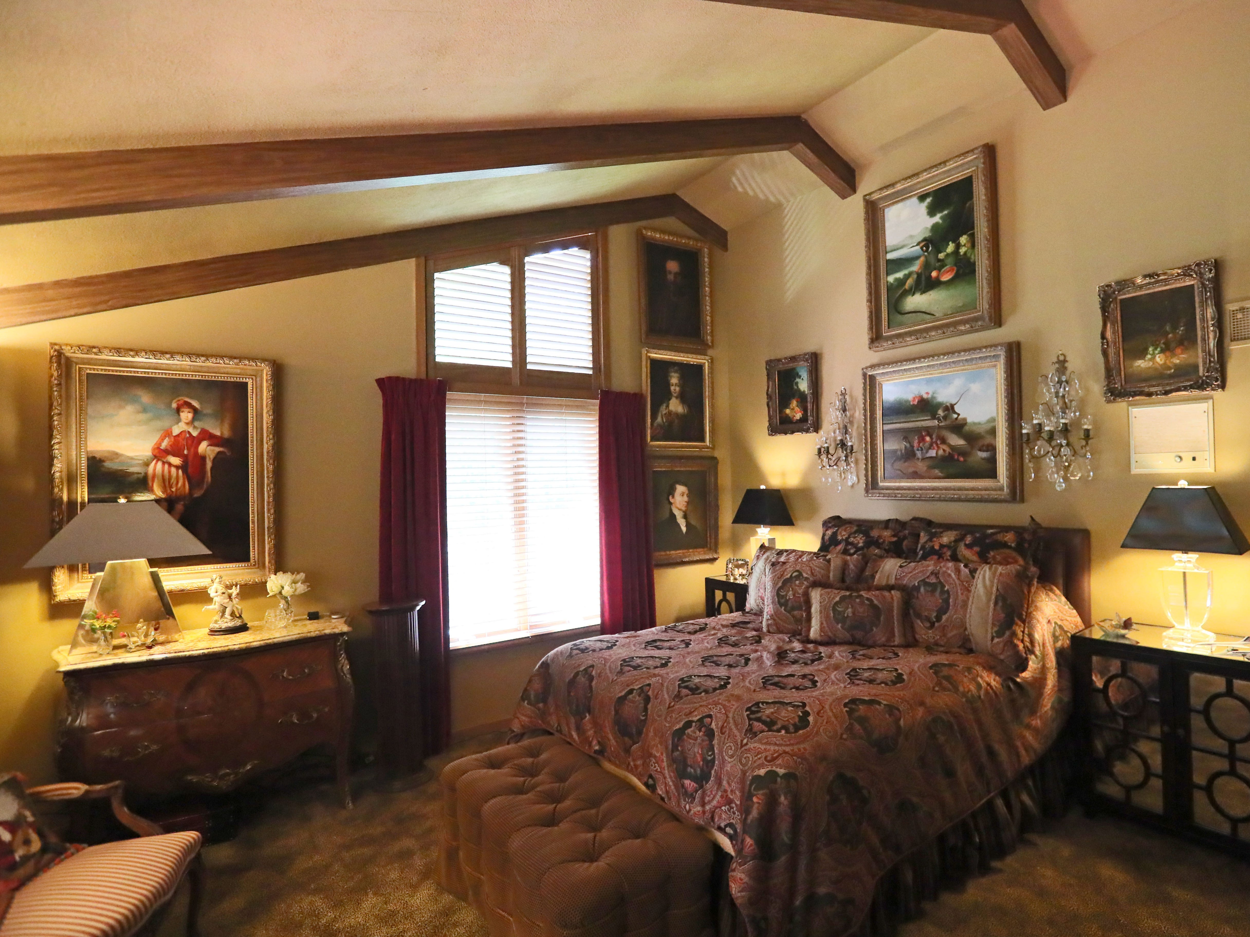 While the living room has primarily more modern art, the other rooms such as this guest bedroom have older oil paintings.