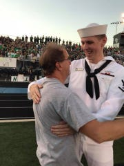 Petty Officer Austin Bonk (right) gives out a hug after surprising his dad and younger brother prior to Greendale's football game on Friday.