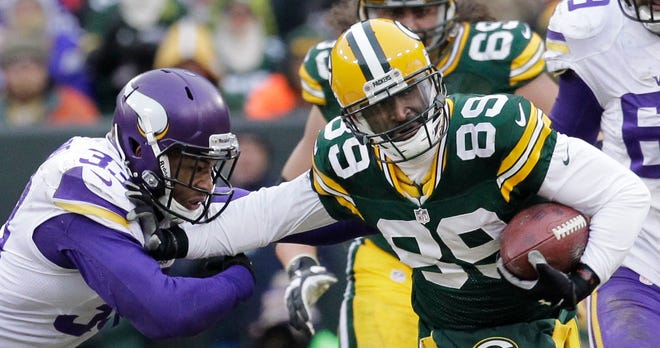 Green Bay Packers wide receiver James Jones (89) picks up 22 yards on a reception while stiff arming Minnesota Vikings safety Jamarca Sanford (33) during overtime in their game Sunday, November 24, 2013 at Lambeau Field in Green Bay, Wis. The Green Bay Packers tied the Minnesota Vikings 26-26.