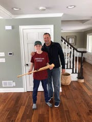 Ian Lang (left) poses with a signed baseball bat that Brewers' third base coach Ed Sedar (right) brought over.