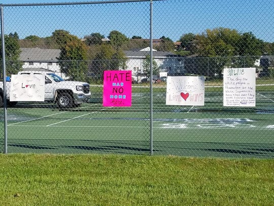 Signs with positive messages made by community members hang on the tennis court fence at Liberty Park in Pewaukee. Community members hung the signs after cleaning up a rash of vandalism at the park.