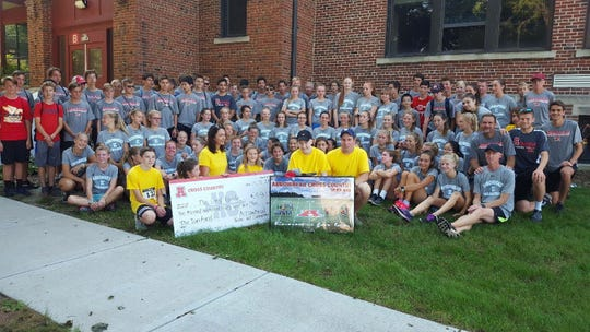 Ian Lang (middle, yellow shirt, black hat) and his family (all in yellow shirts) pose with a check of nearly $11,000 and a poster of the Arrowhead High School boys cross country team spelling out his name with members of the Arrowhead boys and girls cross country teams. It was presented at Harvest Fest at North Lake School Sept. 15.