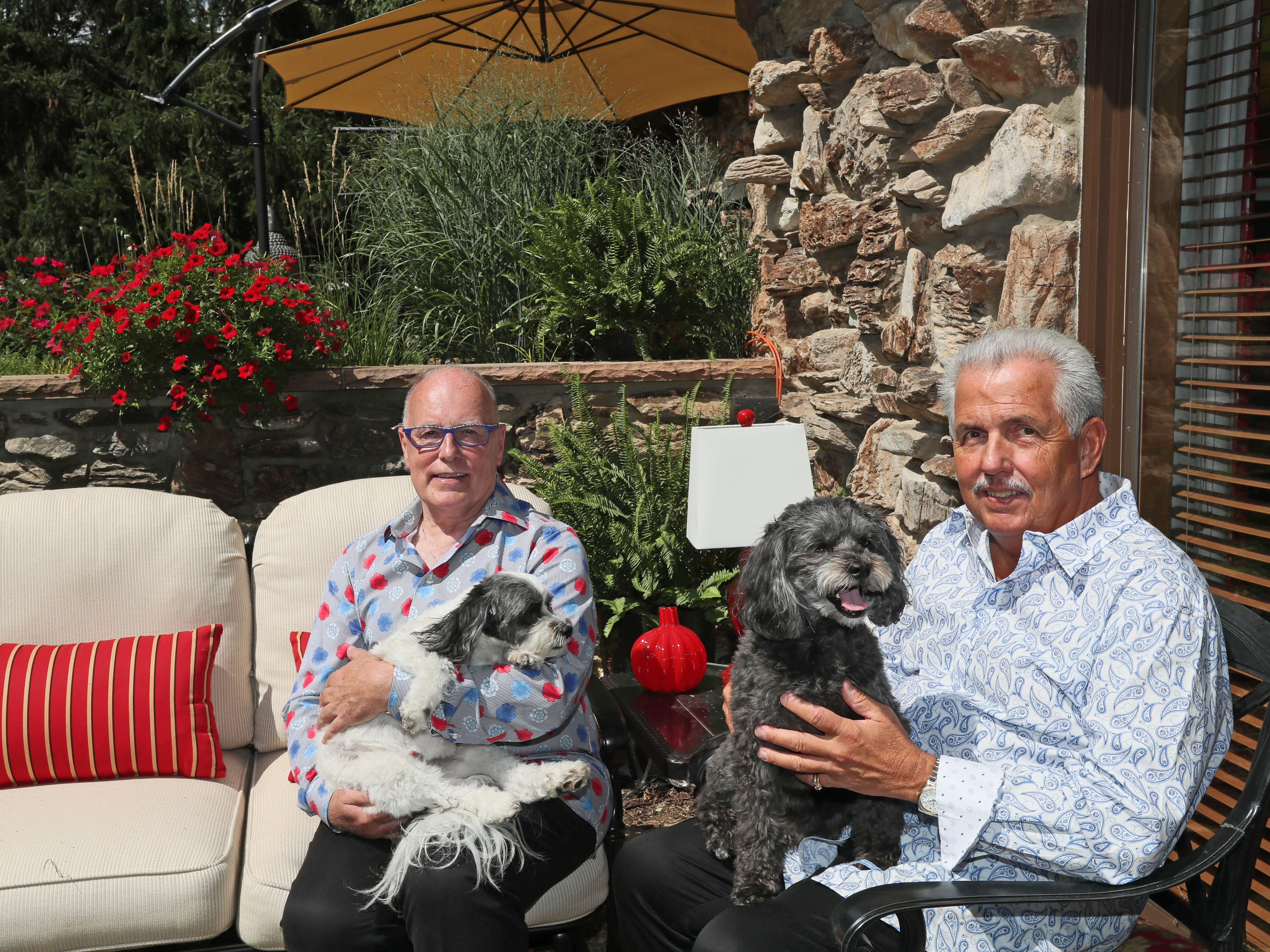 Aubrey Johnson (right), holding the dog Bear, and Jerry Meidl (left) holding the dog Panda, relax on one of the patios at their West Allis home.