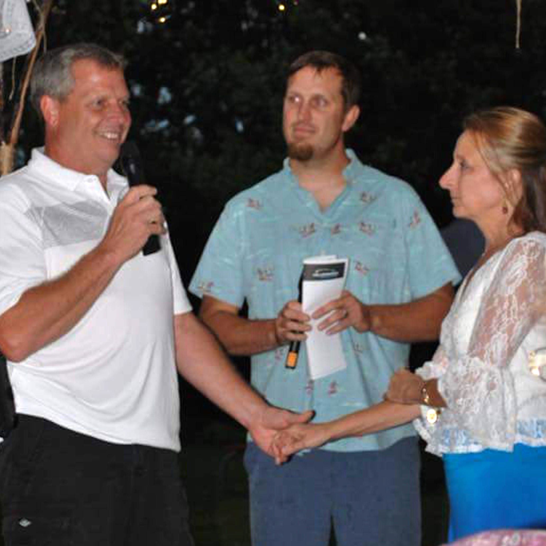 Martin Schmidt, who was ordained online, officiates at the wedding of his birth parents, Dave Lindgren and Michele Newman, in the yard of their Marshfield home on Aug. 4.