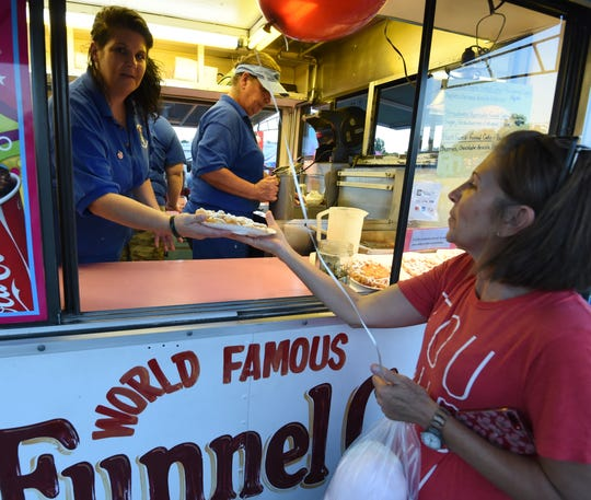 A concession stand worker hands a fair attendee a funnel cake on Thursday night at the Baxter County Fair.