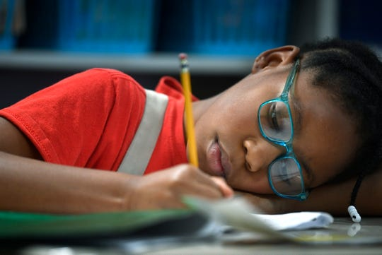 Syrai Alexander finishes a writing assignment at her desk at Fall Hamilton Elementary