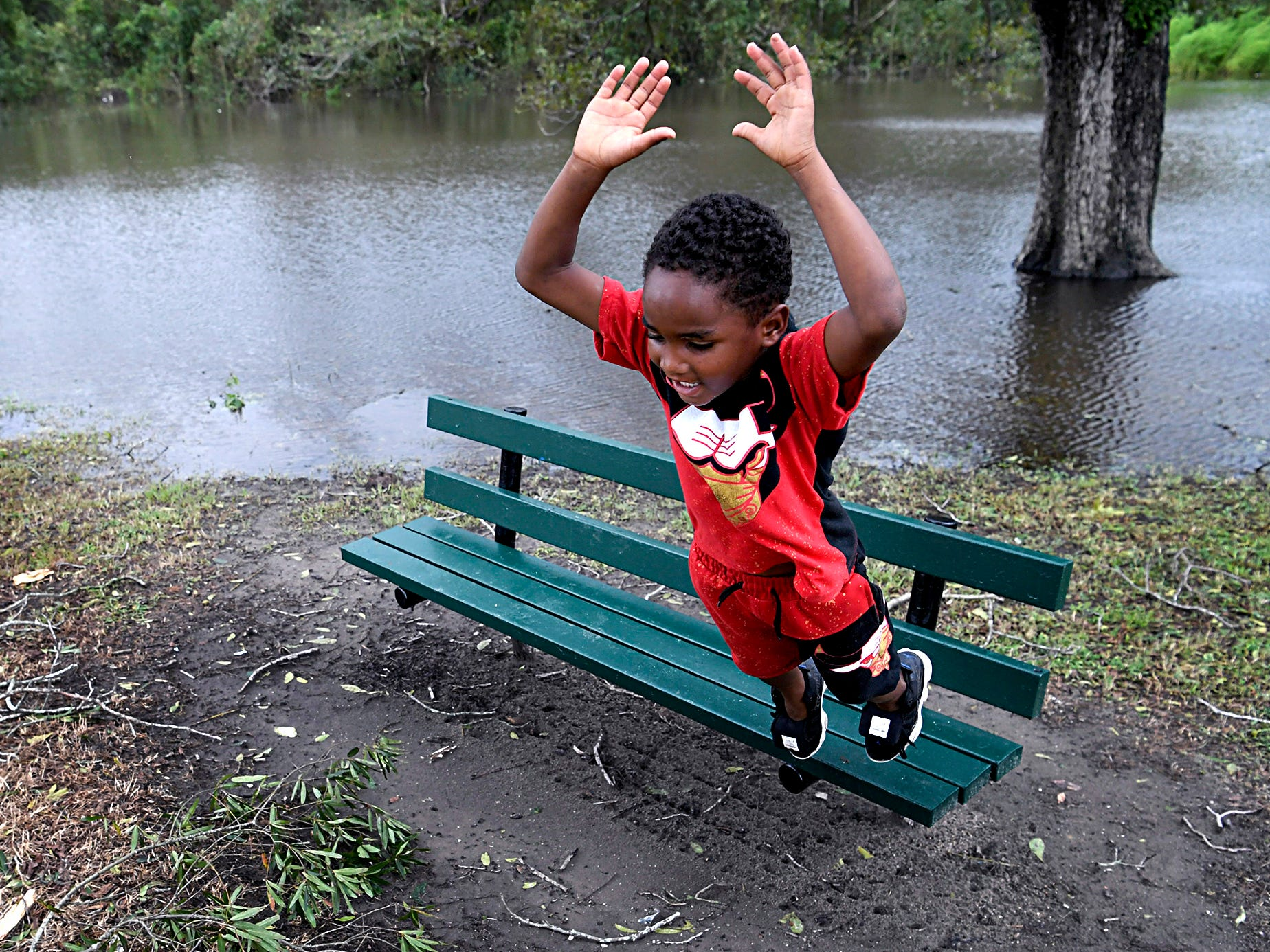 Mamarion Grady, 5, plays on a bench where the Neuse River has flooded a portion of the downtown Kinston, N.C., park on Sunday, Sept. 16 ,2018.