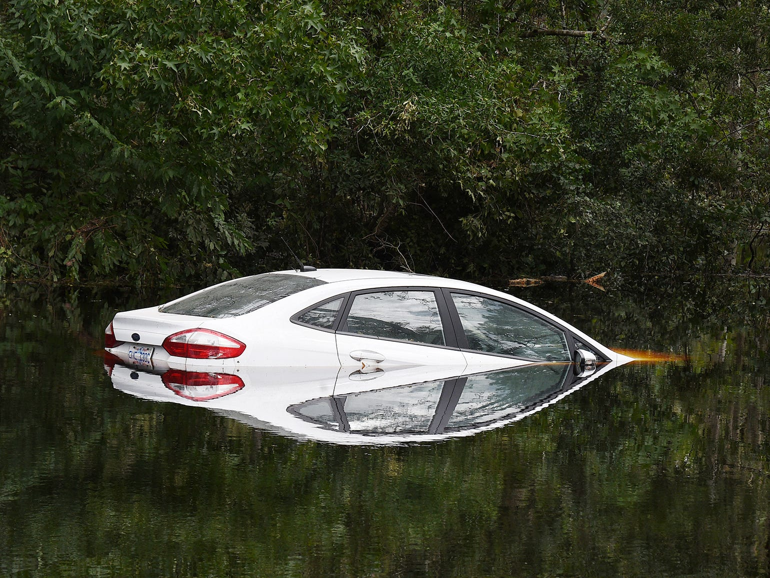 A car is submerger in flood waters in a neighborhood in Newport, NC on Monday Sept. 17, 2018.