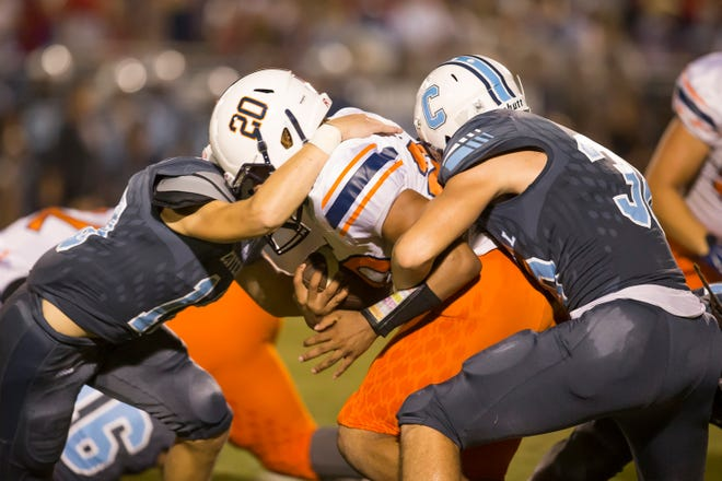 Dickson County's Drequan Vaughn gets wrapped up by Centennial's Wiatt Barber and Sean Hannon.