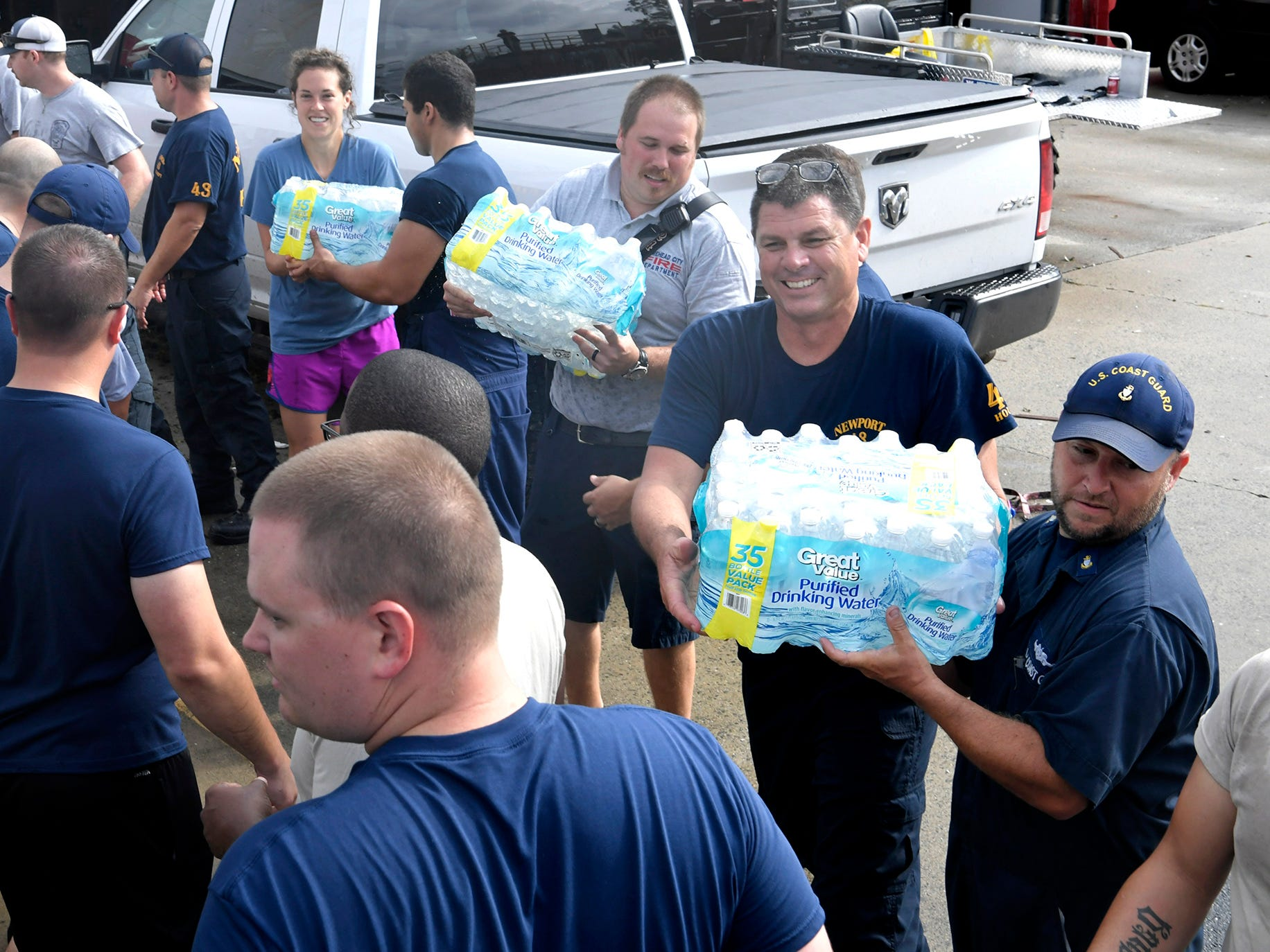 Newport firefighters and Coast Guard personnel help load bottled water at the Newport Fire Department on Monday, Sept. 17, 2018.