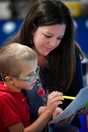 Jiff Burnell helps forth grade student Romie Reeves with a writing assignment at Fall Hamilton Elementary