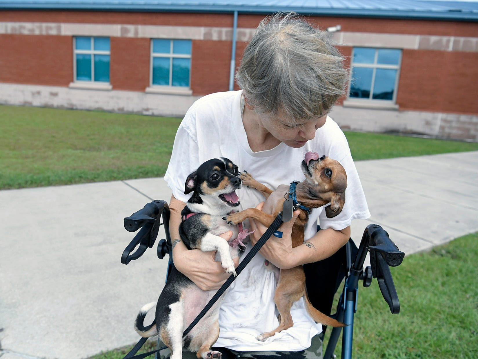 Tinny Bell, 49, holds her dogs, CC and Peanut, at a shelter in Newport, N.C., on Monday, Sept. 17, 2018. Bell was rescued by firefighters after floodwater came into her apartment.