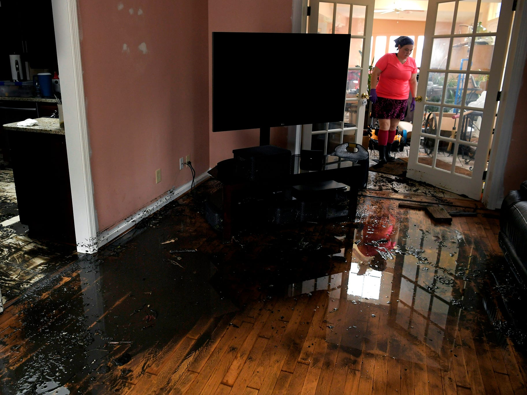 New Bern, N.C., resident Cynthia Downes walks through her flooded home on Sunday, Sept. 16, 2018, following Hurricane Florence.