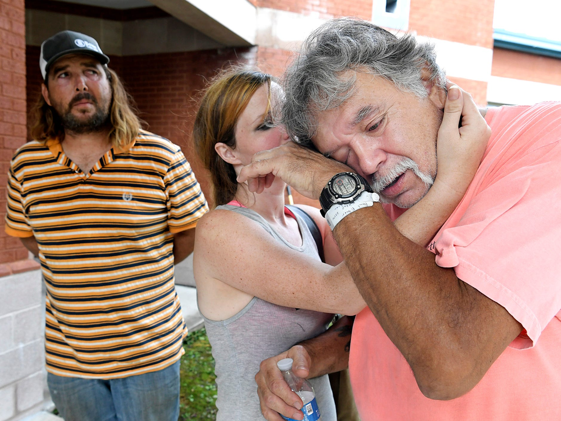 Christian Raup hugs her father-in-law, Paul Pinter, as he cries while recounting how the National Guard rescued him from floodwater last Friday.  Pinter is staying at a shelter at Newport Middle School. PinterÕs son, Mugsy Raup, stands with his wife and father outside the shelter on Monday, Sept. 17, 2018.
