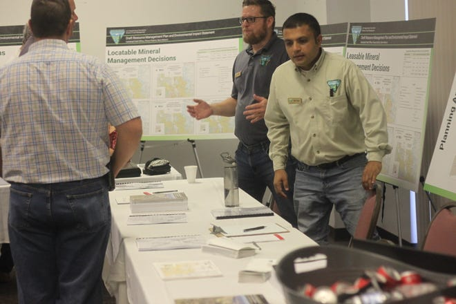 Indra Duha, BLM geologist (left), and BLM petroleum engineer Chris Walls discuss the BLM's resource management plan with members of the public, Sept. 17, 2018 at the Pecos River Village Conference Center.