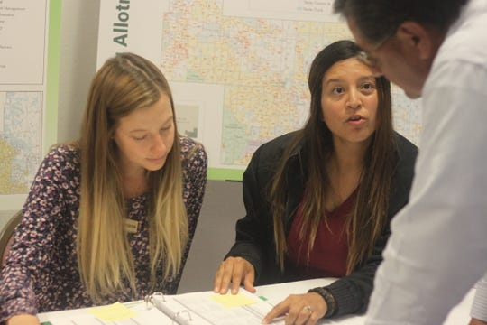 Bureau of Land Management Natural Resource Specialist Jana Marquez (right) explains the BLM's resource management plan, Sept. 17, 2018 at the Pecos River Village Conference Center.