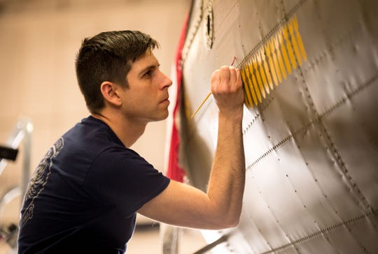 """Museum restoration specialist Casey Simmons paints yellow silhouettes of bombs representing completed missions on the fuselage of the Boeing B-17F """"Memphis Belle"""" during the restoration of the historic aircraft at Wright-Patterson Air Force Base, Ohio, Feb. 1, 2018."""
