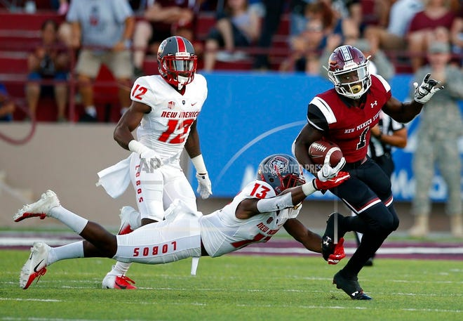 New Mexico State running back Jason Huntley (1) is slowed by New Mexico cornerback Jalin Burrell (13) during the first half of an NCAA college football game in Las Cruces Saturday.