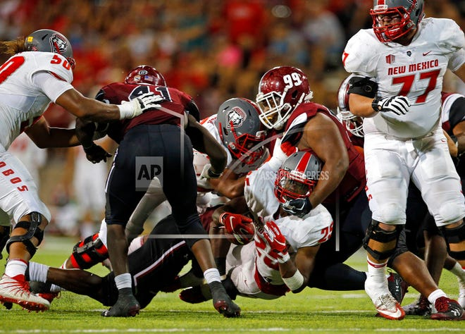 New Mexico running back Tyrone Owens (25) is sacked by New Mexico State defensive lineman Myles Vigne (99) during the second half of an NCAA college football game in Las Cruces, N.M., Saturday.