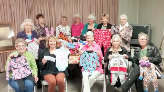 Ruidoso Woman's Club members show some of the pajama donations already received for the Nest domestic violence shelter.