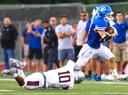 Catholic Central's Ryan Birney (right) makes yards after the catch while being tackled by U-D Jesuit's Carson Hinton (10).