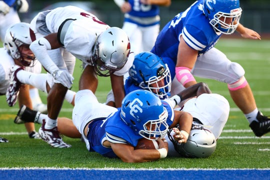 Catholic Central's Bryson Trantham (with ball) plunges to the 1-yard line in Friday's game against U-D Jesuit.