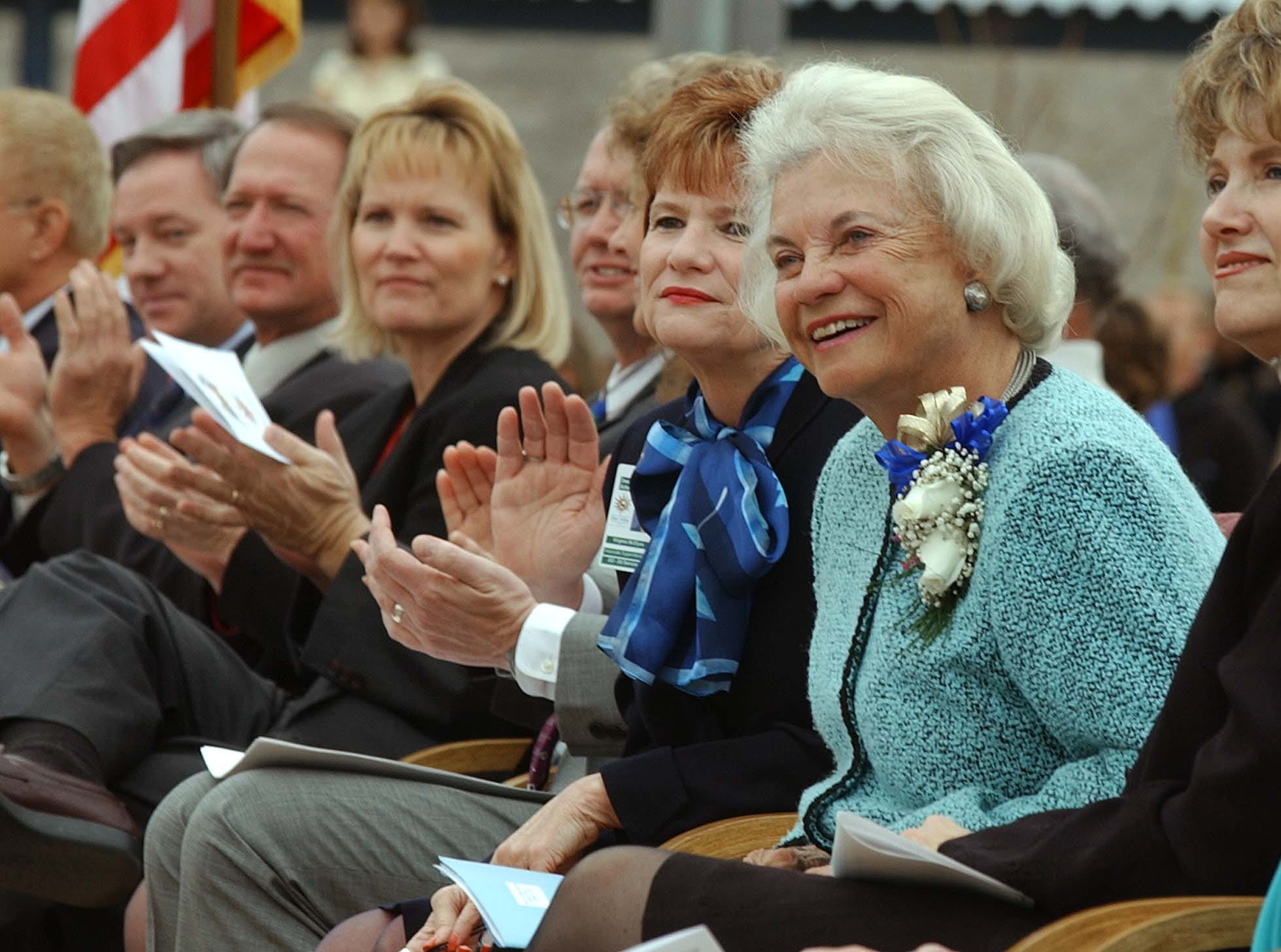U.S. Supreme Court Justice Sandra Day O'Connor, along with Deer Valley School District members, listen to students of the Sandra Day O'Connor High School choir during a dedication for the recently opened school on Feb. 12, 2003, in north Phoenix.