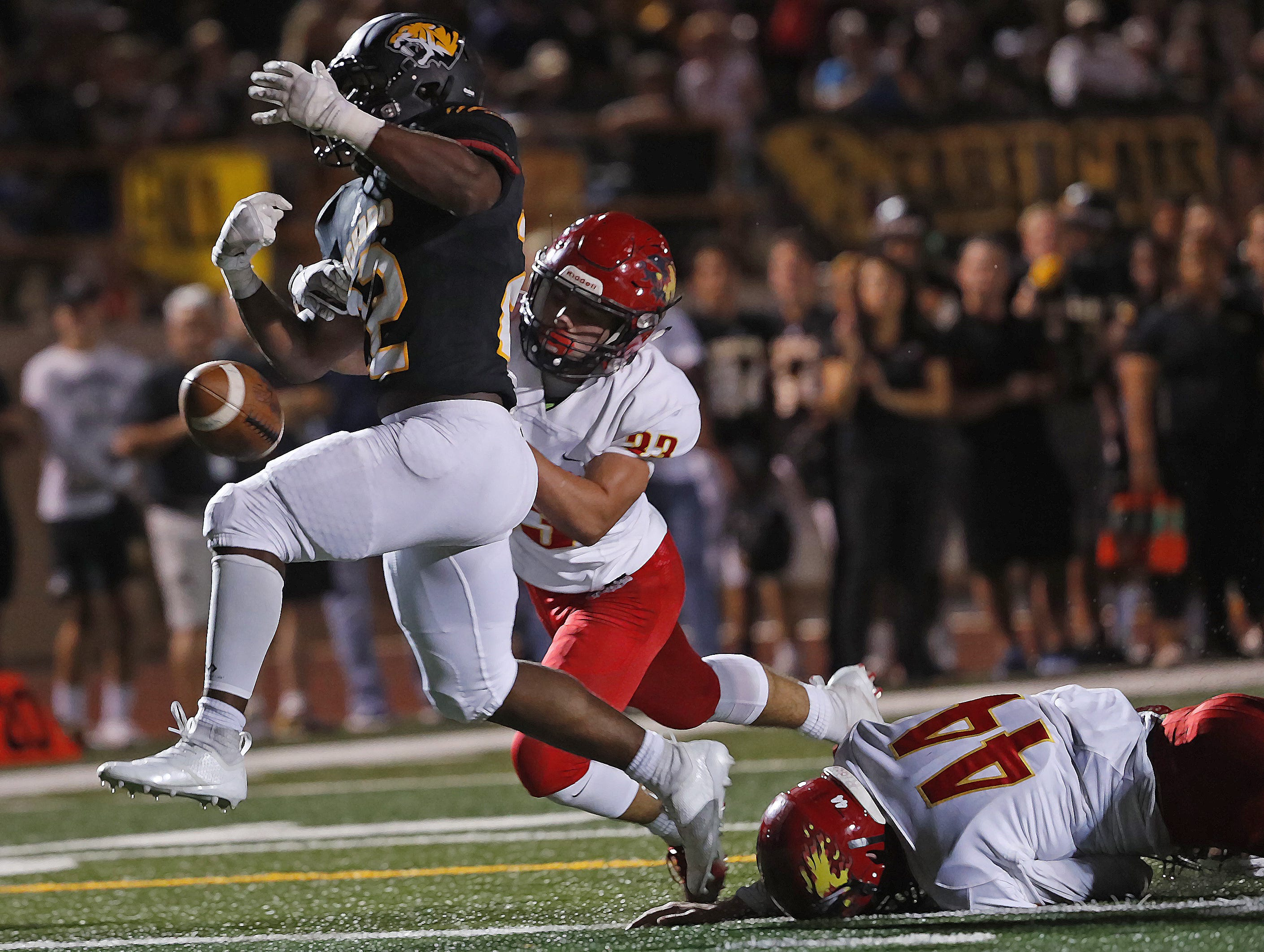 Chaparral's Braxen Tessler (33) forces a fumble from Saguaro's Israel Benjamin (22) right before the end zone during the first half at Saguaro High School in Scottsdale, Ariz. on Sept. 14, 2018.