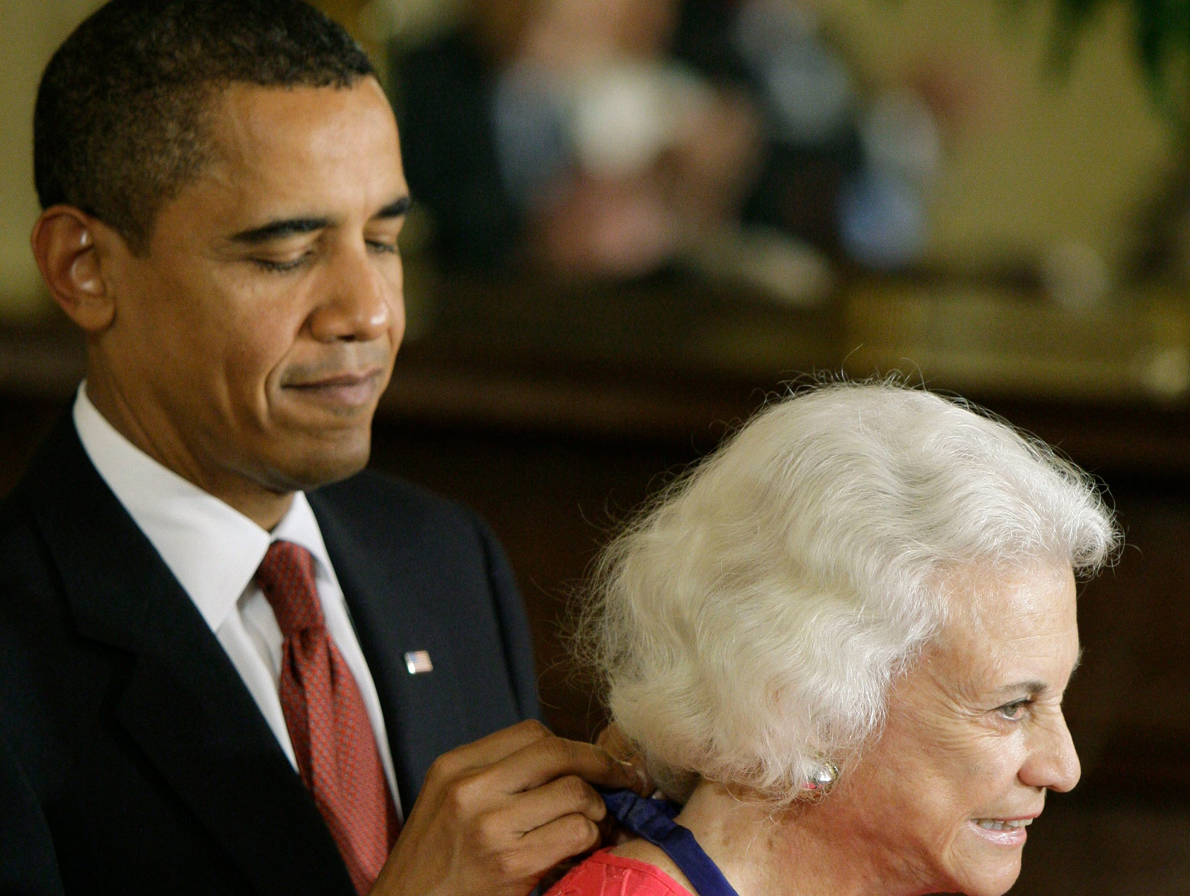 President Barack Obama places a 2009 Presidential Medal of Freedom around the neck of former Supreme Court Justice Sandra Day O'Connor, Wednesday, Aug. 12, 2009, during a ceremony in the East Room of the White House in Washington.