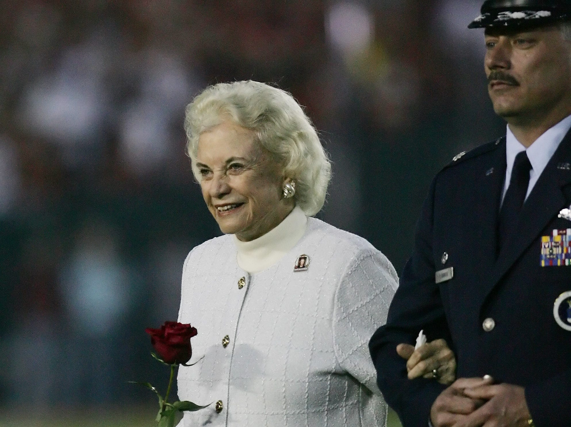 Supreme Court Justice Sandra Day O'Connor is escorted from the field following the coin toss before Texas met Southern California in the Rose Bowl, the national championship college football game in Pasadena, Calif., Wednesday, Jan. 4, 2006.