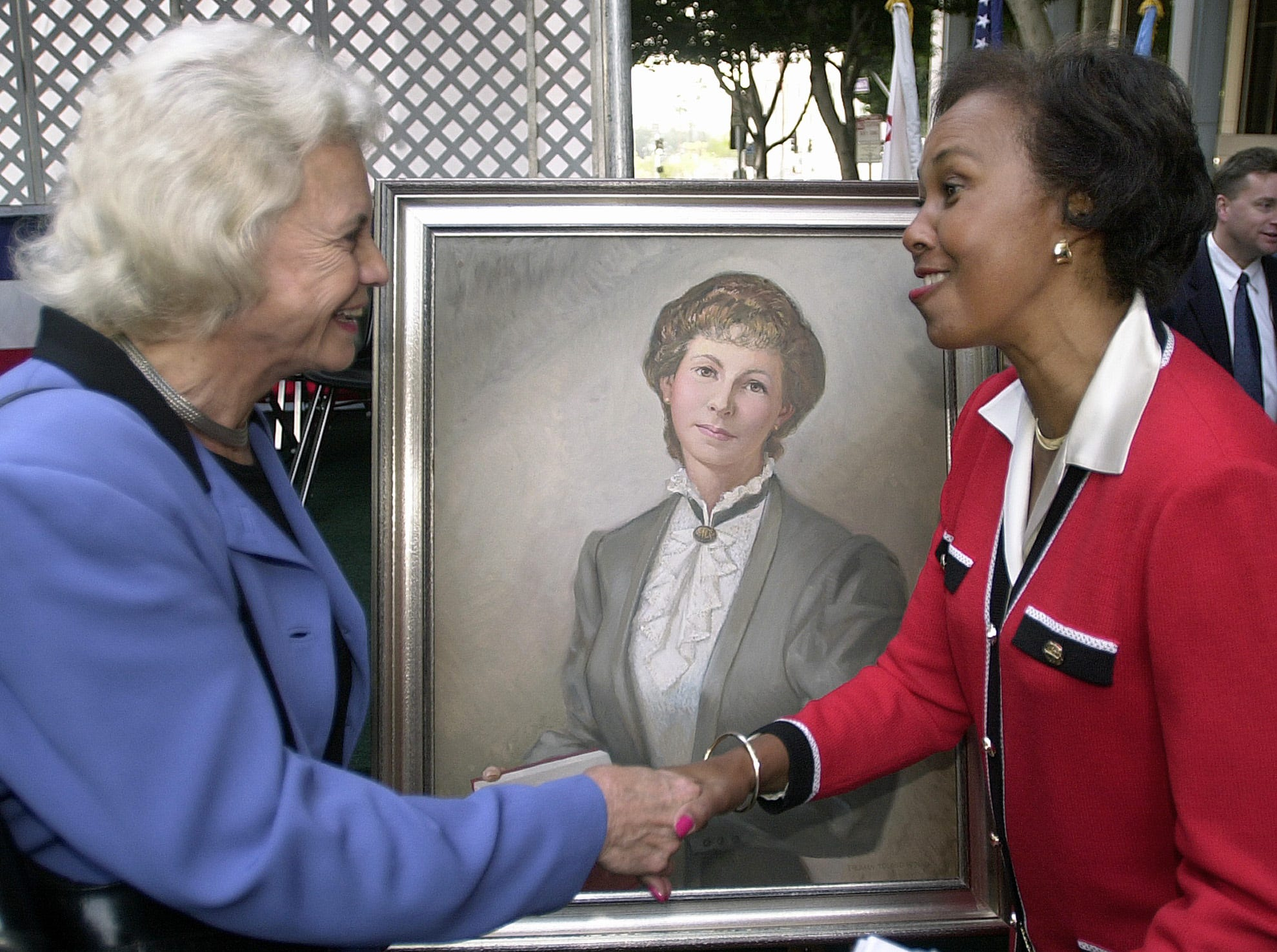 Supreme Court Justice Sandra Day O'Connor shakes hands with Los Angeles Supervisor Yvonne Braithwaite Burke as they pay tribute to law pioneer, Clara Shortridge Foltz, seen in the painting, Friday, Feb. 8, 2002, in downtown Los Angeles. The Los Angeles Criminal Courts building was renamed to the Clara Shortridge Folz Criminal Justice Center to commemorate California's first female lawyer.