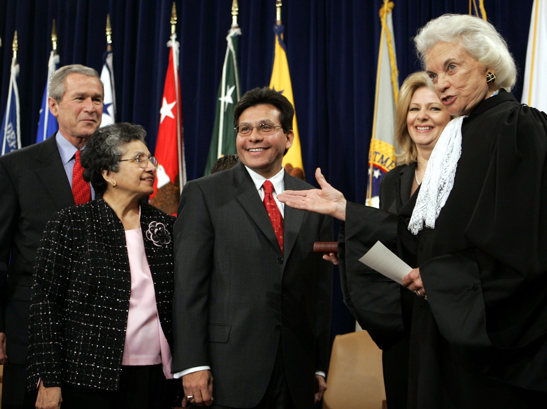 Supreme Court Justice Sandra Day O'Connor, right, presents Attorney General Alberto Gonzales, center,  during a ceremony at the Justice Department in Washington, with President Bush, left, his mother Maria Gonzales, second from left, and his wife Rebecca, second from left,  Monday, Feb. 14, 2005.