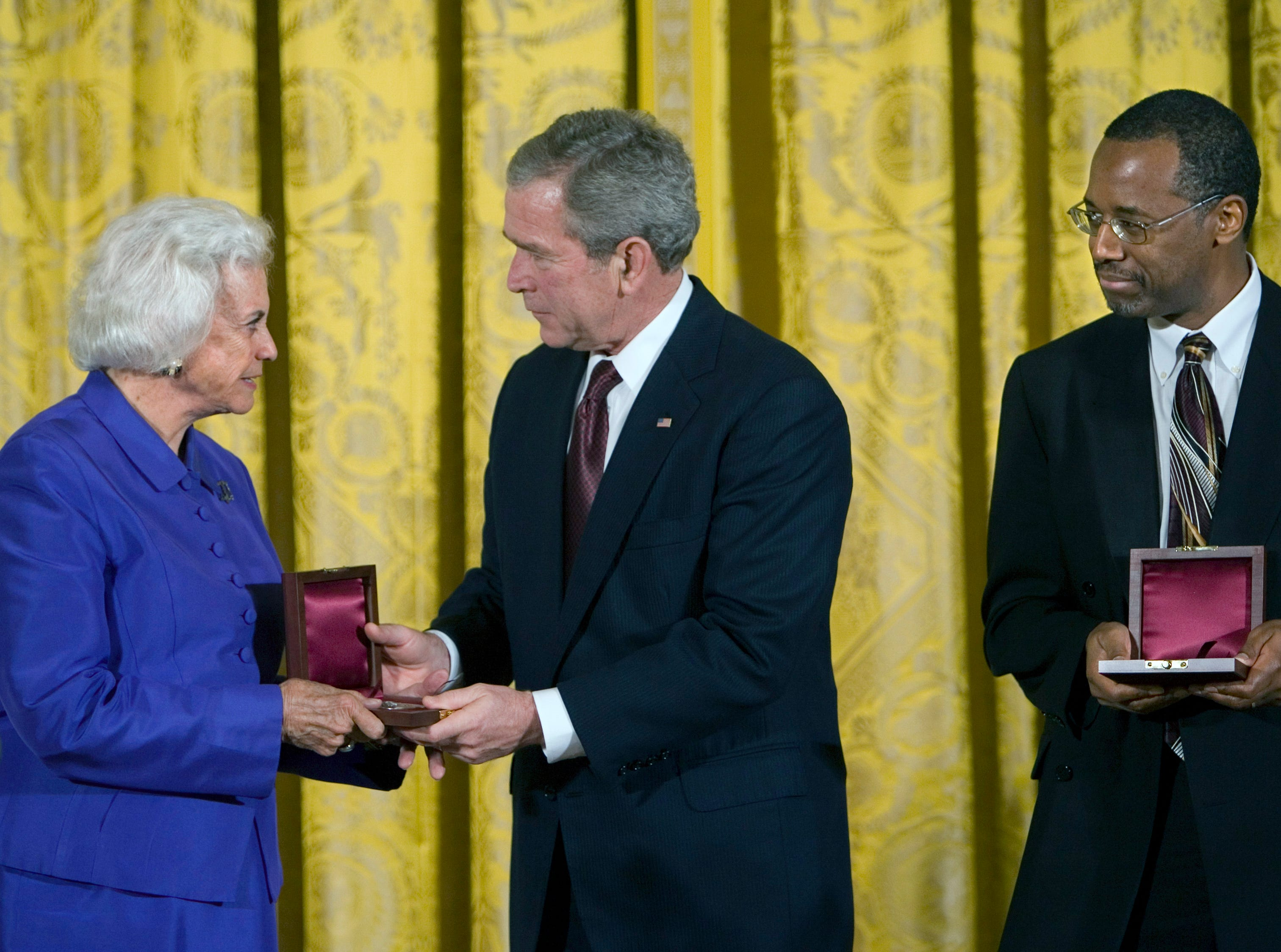 President Bush presents The Lincoln Medal to retired U.S. Supreme Court Justice Sandra Day O'Connor, left, and Dr. Benjamin Carson, right, a renowned pediatric neurosurgeon at Johns Hopkins Children's Center in Baltimore, during  a ceremony in honor of Abraham Lincoln's 199th birthday, in the East Room of the White House in Washington, Sunday, Feb. 10, 2008.