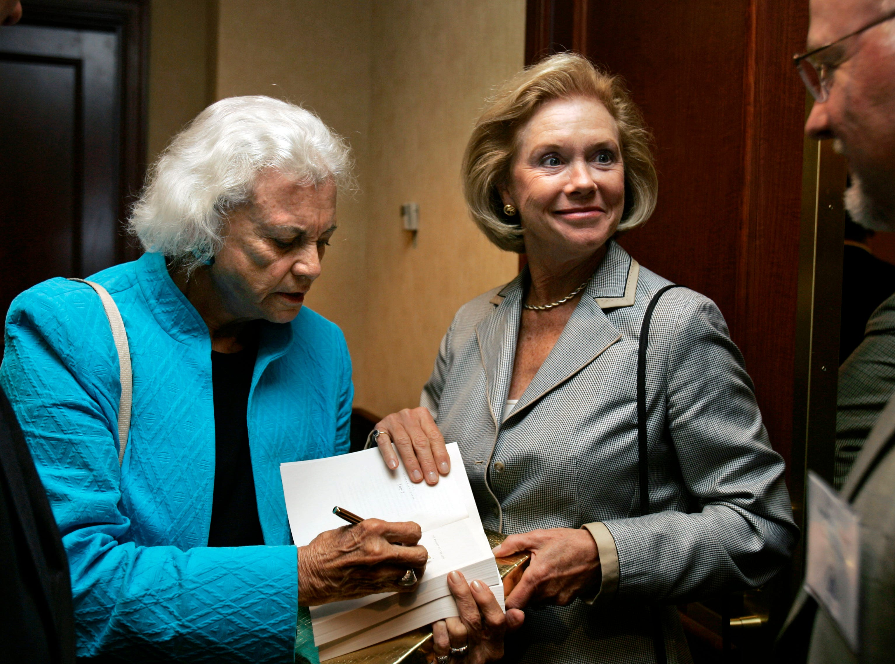U.S. Circuit Judge Marjorie O. Rendell, second from left, holds a book to be autographed for retired U.S. Supreme Court Justice Sandra Day O'Connor after a meeting of Pennsylvania judges and lawyers in Harrisburg, Pa., Wednesday, Sept., 19, 2007.