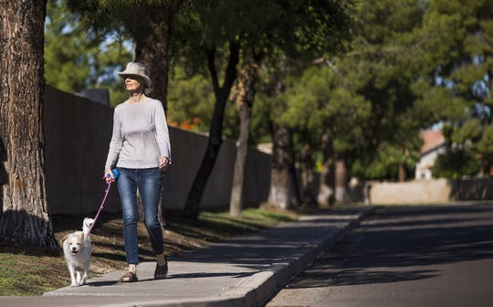 Michelle Gailiun walks her dog, Junie B, in a Peoria neighborhood, where an HOA has told residents some of the old trees may have to be cut down to prevent more damage to walls.