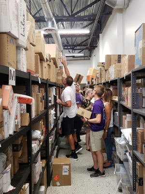 Basketball coach Dan Majerle helps out in the Grand Canyon Univeresity mailroom.