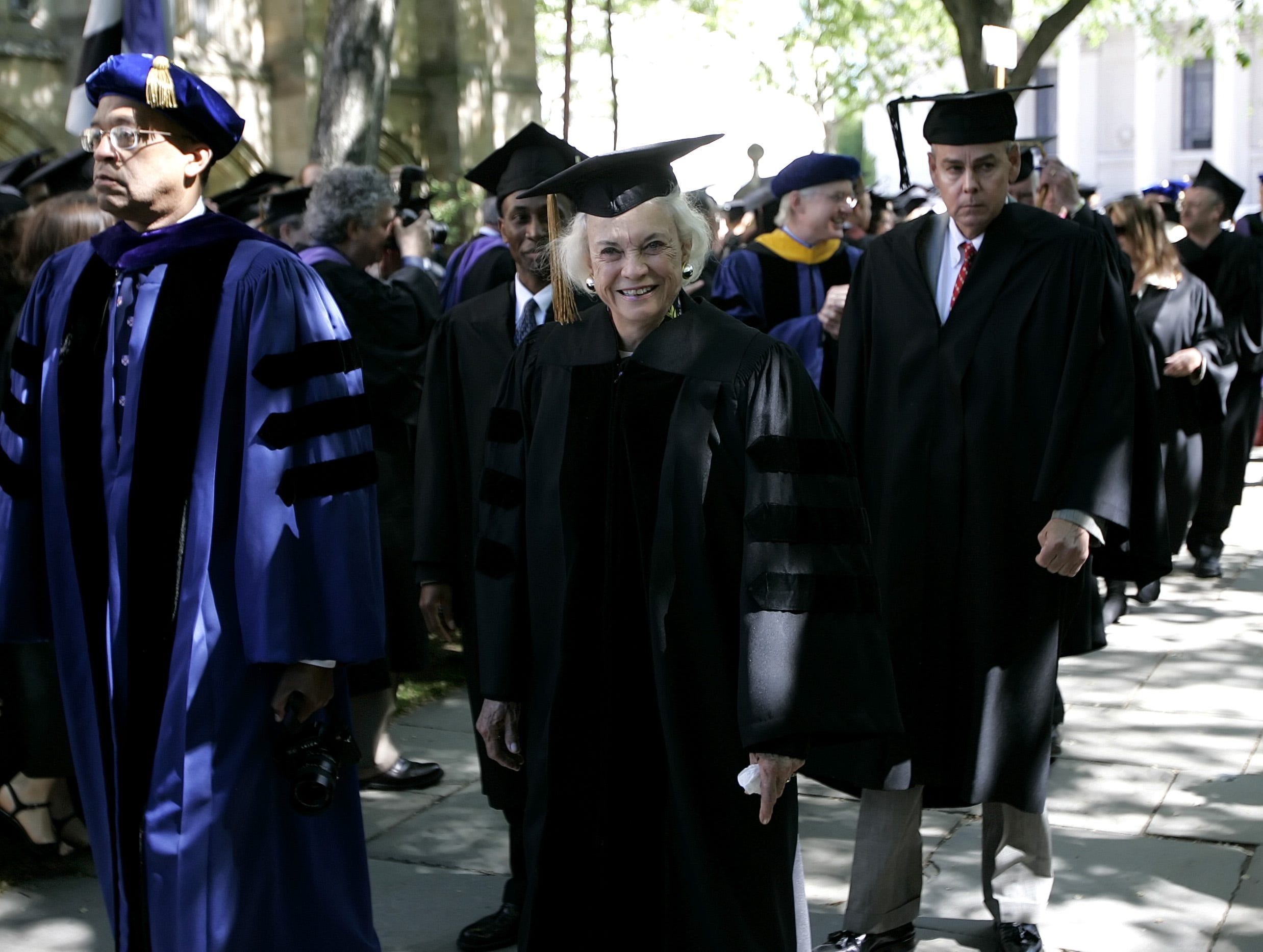 Retired U.S. Supreme Court Justice Sandra Day O'Connor, center, smiles as she walks in the academic procession on the campus at Yale University in New Haven, Conn., Monday, May 22, 2006. O'Connor was awarded an honorary Doctor of Laws degree.