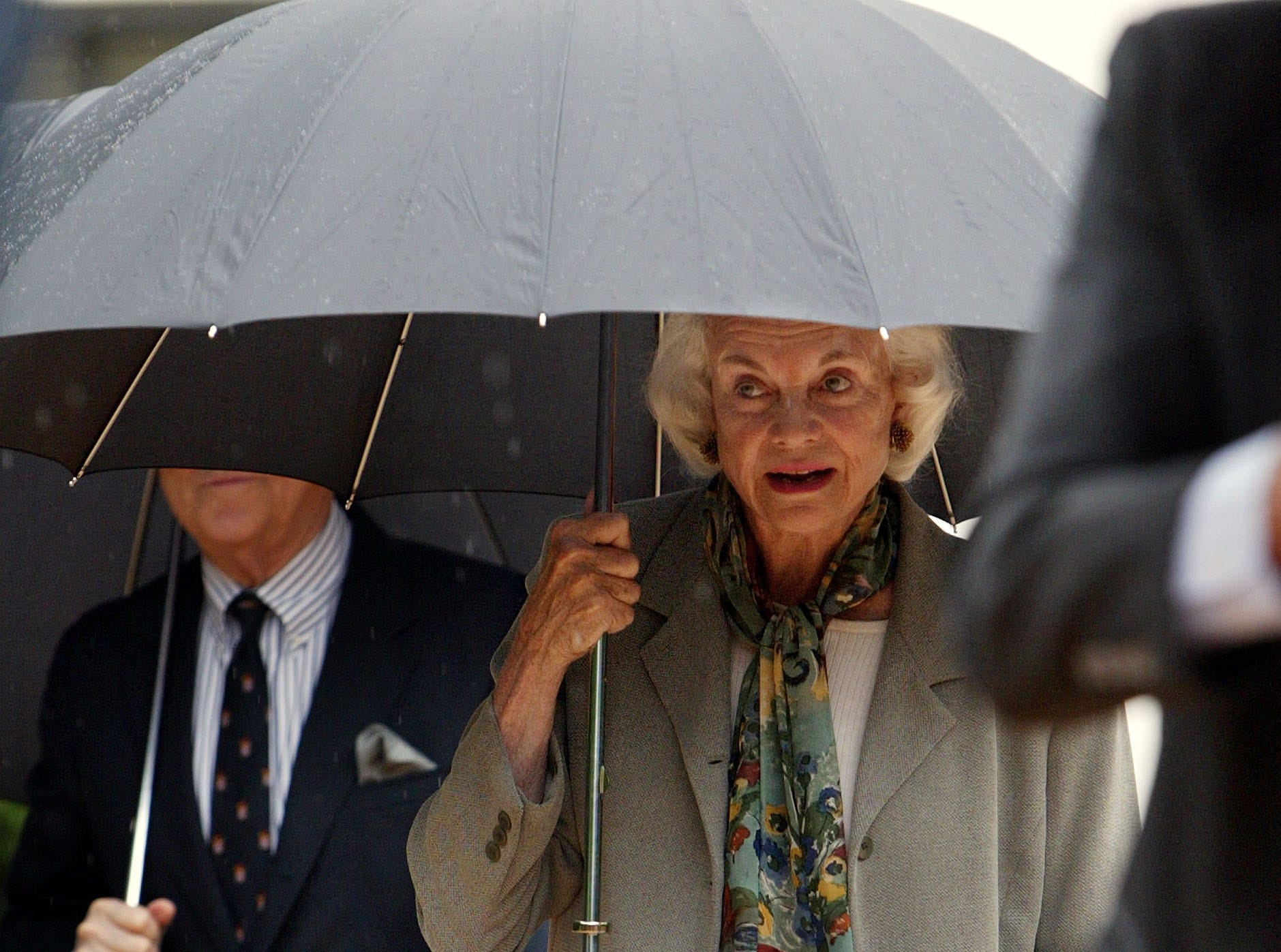 Supreme Court Associate Justice Sandra Day O'Connor, center, arrives in a pouring rain, Tuesday, June 17, 2003, at a groundbreaking ceremony for a new section of the Supreme Court in Washington. It is phase one of a five-year restoration.