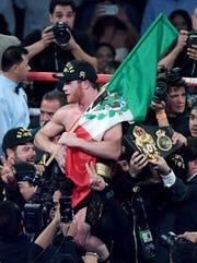 'Canelo' celebra la victoria con una bandera de México.