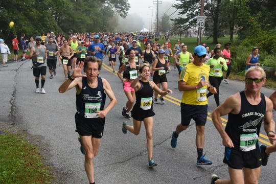 Runners, including Bill Rodgers waving, take part in the 40th Dutchess County Classic half-marathon race on Sunday in LaGrangeville.